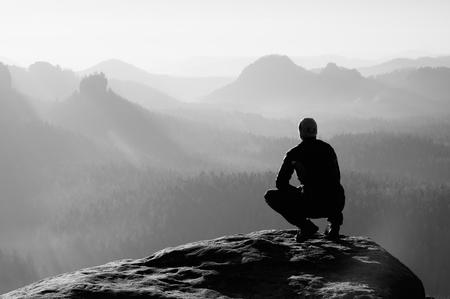 검은 운동복에 젊은 남자가 절벽의 가장자리에 앉아 울부 짖는 계곡을 안개 낀 찾고 있습니다