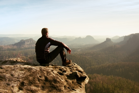 foggy hill: Young man in black sportswear is sitting on cliffs edge and looking to misty valley bellow