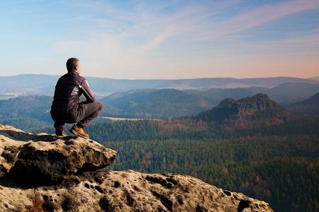 깊은 안개 낀 계곡의 울부 짖는 소리의 공중보기 바위의 상단에 성인 남자를 등반