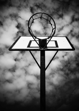 neglect: Old neglect basketball backboard with rusty hoop above street court. Blue cloudy sky in bckground.
