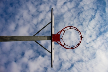 iron hoops: Old neglect basketball backboard with rusty hoop above street court. Blue cloudy sky in bckground.
