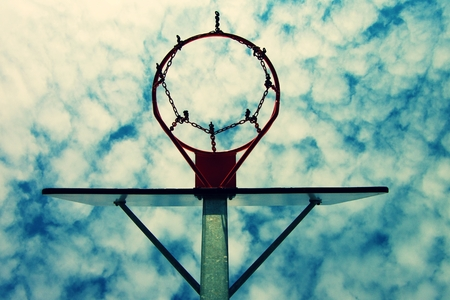 backboard: Old neglect basketball backboard with rusty hoop above street court. Blue cloudy sky in bckground.