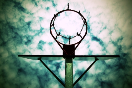 swish: Old neglect basketball backboard with rusty hoop above street court. Blue cloudy sky in bckground.