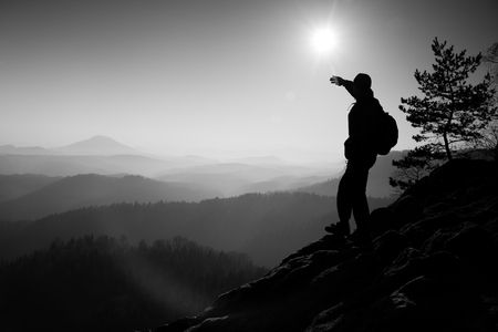 empires: Sunny morning. Hiker is standing on the peak of rock in rock empires park and watching over the misty and foggy morning valley to Sun.