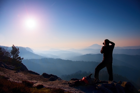valley below: Professional photographer takes photos with mirror camera on peak of rock. Dreamy fogy landscape, spring orange pink misty sunrise in a beautiful valley below Stock Photo