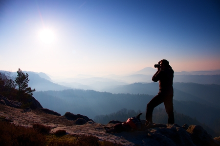 Professional photographer takes photos with mirror camera on peak of rock. Dreamy fogy landscape, spring orange pink misty sunrise in a beautiful valley below Фото со стока