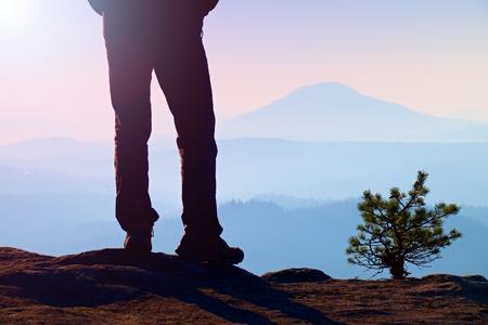 rocky peak: Man hiker legs in tourist boots stand on mountain rocky peak