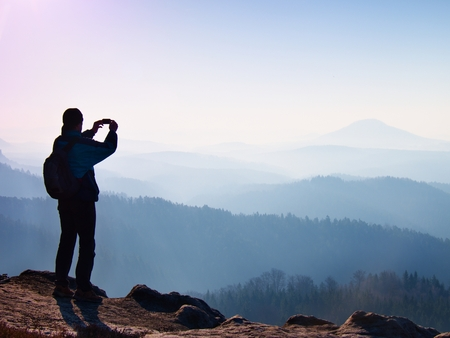 valley below: Tourist takes photos with smart phone on peak of rock. Dreamy fogy landscape, spring orange pink misty sunrise in a beautiful valley below