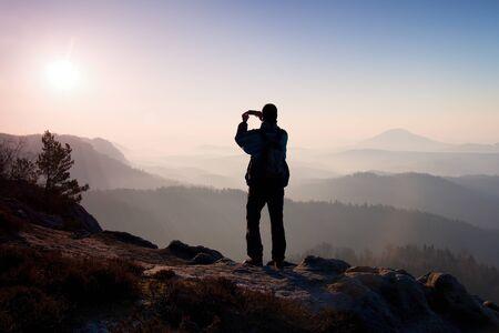 niño con mochila: Turismo toma fotos con el teléfono inteligente en el pico de roca. Paisaje fogey soñadora, primavera naranja amanecer brumoso color rosa en un hermoso valle Foto de archivo