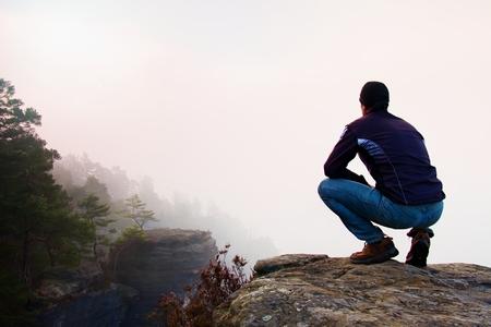 en cuclillas: Caminante en cuclillas positionon y el rock, disfrutar del paisaje Foto de archivo
