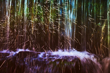 Shinning drops. Cascade of small weir on mountain stream, big mossy boulders.