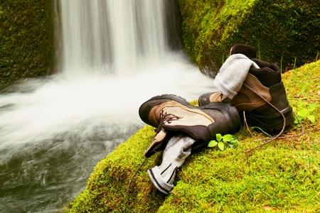 calcetines: Altas botas de caminante y calcetines grises sudorosas. Descansando en la roca en el arroyo de monta�a agradable Foto de archivo