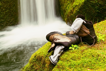 outsole: Hiker high boots and sweaty grey socks. Resting on the boulder at the  nice mountain stream