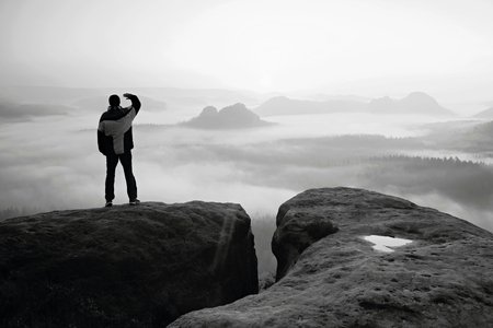 cold weather: Moment of loneliness. Man on the rock empires  and watch over the misty and foggy morning valley.