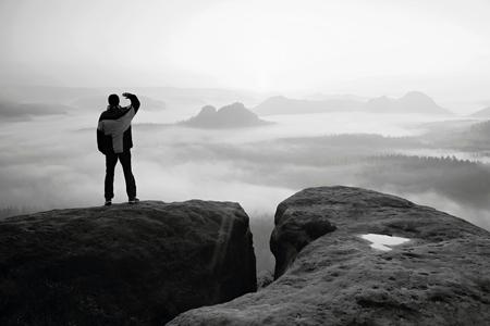 persona pensando: Momento de la soledad. Hombre en los imperios de rock y velar� por el valle brumoso y brumoso ma�ana.