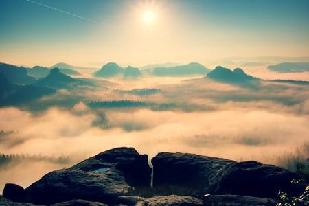Fantastic dreamy sunrise on the top of the rocky mountain with the view into misty valley