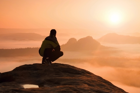 Mounrains の谷の上の夜明けを楽しみながら岩のピークの上に座って男性ハイカーの背面図