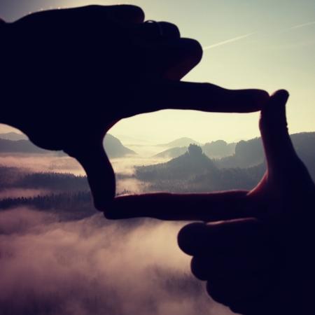 reflexionando: Close up of hands making frame gesture. Blue misty valley bellow rocky peak. Sunny spring daybreak in rocky mountains.