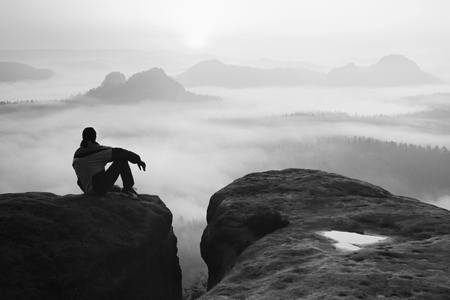 rocky peak: Rear view of male hiker sitting on the rocky peak  while enjoying a daybreak above mounrains valley