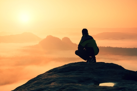 Rear view of male hiker sitting on the rocky peak  while enjoying a daybreak above mounrains valley