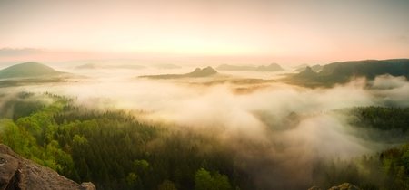 valley below: Landscape misty panorama. Fantastic dreamy sunrise on rocky mountains with view into misty valley below
