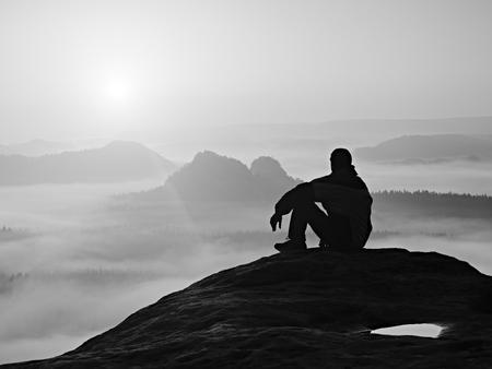 rocky peak: Hiker in black on the rocky peak. Wonderful daybreak in mountains, heavy orange mist in deep valley. Man sit on the rock. Stock Photo