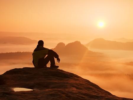 rock: Hiker in black on the rocky peak. Wonderful daybreak in mountains, heavy orange mist in deep valley. Man sit on the rock and watch over the fog .