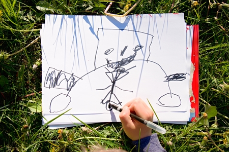 Close up view of child's hand drawing colorful ornaments on paper. Notebook in fresh grass of meadow.