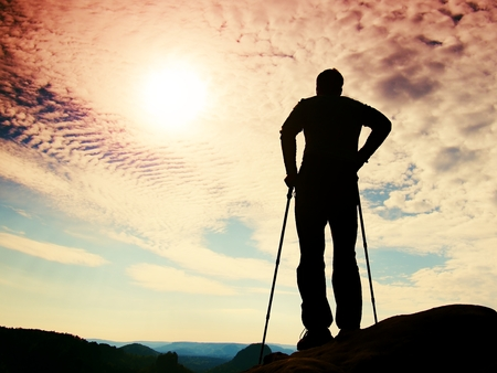 rocky point: Tourist sports with poles in hands stand on rocky view point and watching deep into the misty valley bellow. Sunny spring daybreak in the Rocky Mountains. Stock Photo