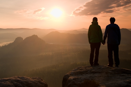 empires: Couple in love enjoying tender moments during sunset. Young pair of hikers hand in hand on the peak of rock empires park and watch over the misty and foggy mornings Sun Valley