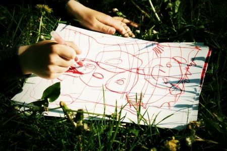 jardin de infantes: Cierre de vista de dibujo adornos de colores sobre papel la mano del ni�o. Notebook en hierba fresca del prado. Foto de archivo