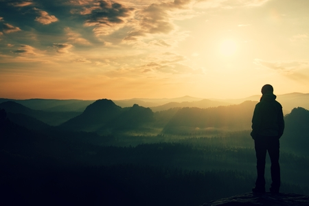 Alone young girl tourist feast daybreak on the sharp corner of sandstone rock and watch over valley's Sun. 스톡 콘텐츠