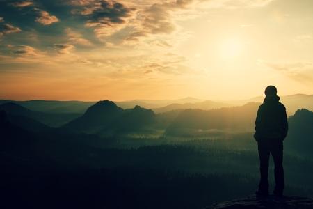 Ensam ung flicka turist fest gryningen på den skarpa hörn av sandsten rock och vaka över dalens Sun.