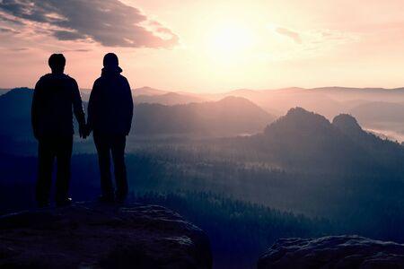 mundo manos: Joven pareja de excursionistas de la mano en la cima de los imperios Rock Park y velar por la niebla y la niebla por la ma�ana valle a Sun. Foto de archivo