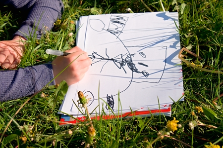 jardin de infantes: Close up view of childs hand drawing colorful ornaments on paper. Notebook in fresh grass of meadow.