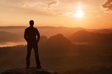 muž: Hiker v černém stánku na vrcholu ve skále impéria parku a sledování přes mlhavé a mlhavého rána údolí k Sun. Reklamní fotografie