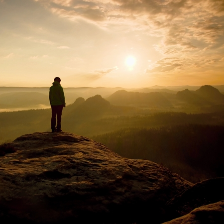 niño parado: Caminante de pie en la esquina aguda de roca arenisca en imperios Rock Park y velar por la niebla y la niebla por la mañana valle a Sun. Foto de archivo
