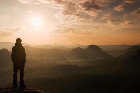 man thinking: Sad girl stand on the sharp corner of sandstone rock and watch over valleys Sun. Stock Photo