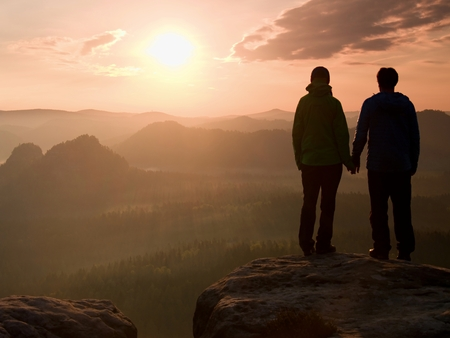 empires: Young pair of hikers hand in hand on the peak of rock empires park and watch over the misty and foggy morning valley to Sun. Stock Photo