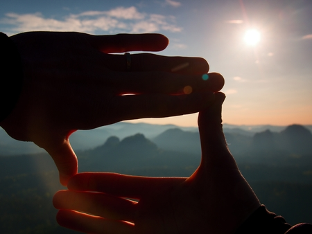 Tourist make frame with palms and fingers on Both Hands. Hiker stand on rocky view point, daybreak in the Rocky Mountains. Stock Photo