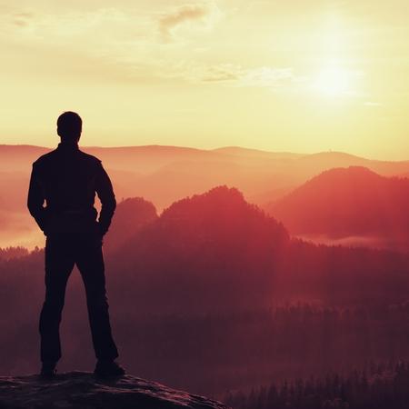 reflexionando: Caminante en soporte negro en el pico en la roca imperios parque velar por Sun Valley la niebla y niebla de la ma�ana