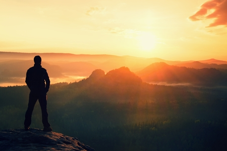 outdoor sport: Hiker stand on the sharp corner of sandstone rock in rock empires park and watching over the misty and foggy morning valley to Sun.