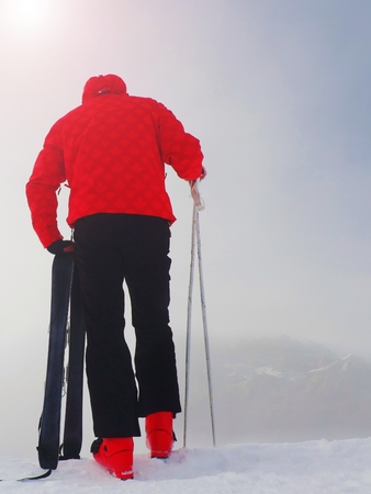 winter jacket: Skier in red winter jacket with  small fun skis stay in snow in mountains. Fogy winter day at peak. Stock Photo