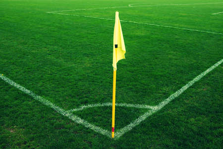 wind blowing: Yellow flag in corner of football playground, lazy wind blowing