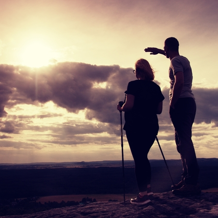 marvellous: Couple enjoying marvellous moments during sunset . Young pair of hikers on the peak of rock empires park and watch over valley to Sun. Stock Photo