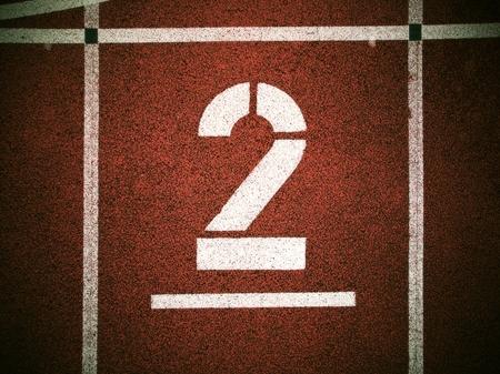 racetrack: Big white track number on red rubber racetrack. Gentle textured running racetracks in small outdoor stadium.