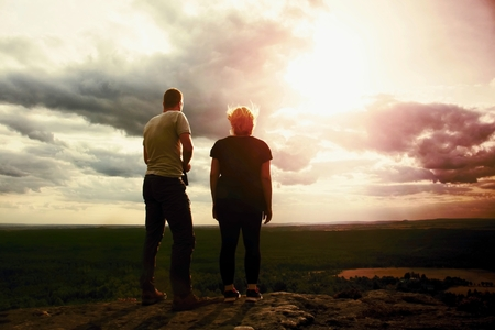 empires: Couple enjoying marvellous moments during sunset . Young pair of hikers on the peak of rock empires park and watch over valley to Sun. Stock Photo