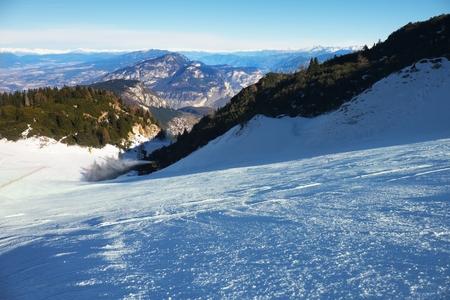 powder snow: Snowmaking on slope. Skier near a snow cannon making fresch powder snow. Mountain ski resort and winter calm mountain landscape.