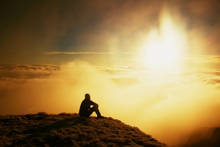 Tall tourist in black on the peak of the world . Heavy orange mist bellow in valley. Dreamy daybreak in mountains. Stock Photo