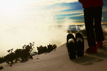 winter jacket: Skier in red winter jacket with  fun snowshoes stay in snow in mountains. Fogy winter day at peak.